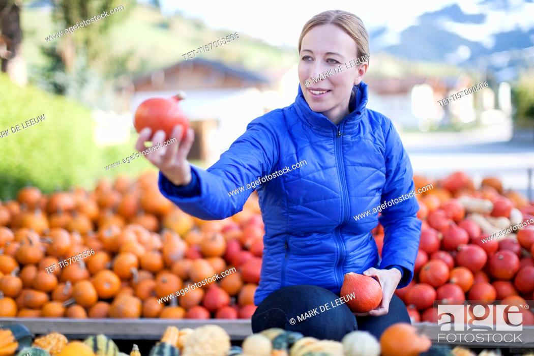 Stock Photo: Austria, Salzburger Land, Maria Alm, Mature woman in blue jacket holding red vegetables.
