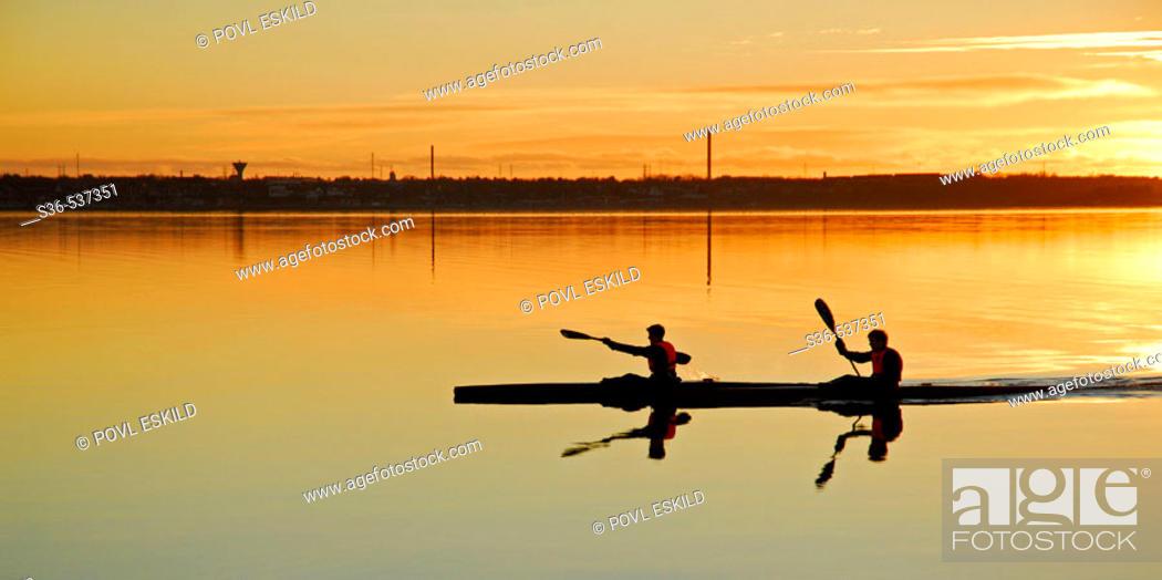 Stock Photo: Two paddelers kayaking on Struer bay, Limfjorden, western Jutland, Denmark. Sunset and golden colors.