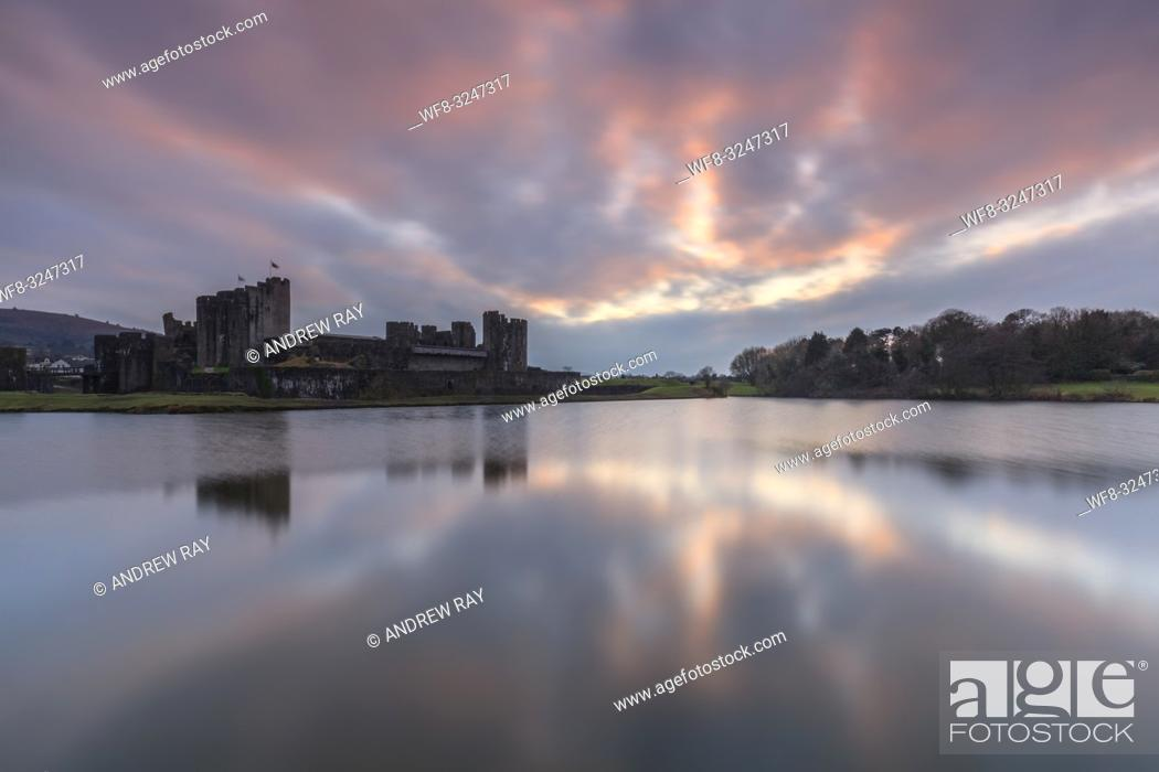 Stock Photo: Sunset over Caerphilly Castle in South Wales, captured on an evening in mid February. A long shutter speed was utilised to flatten ripples on the surface of the.
