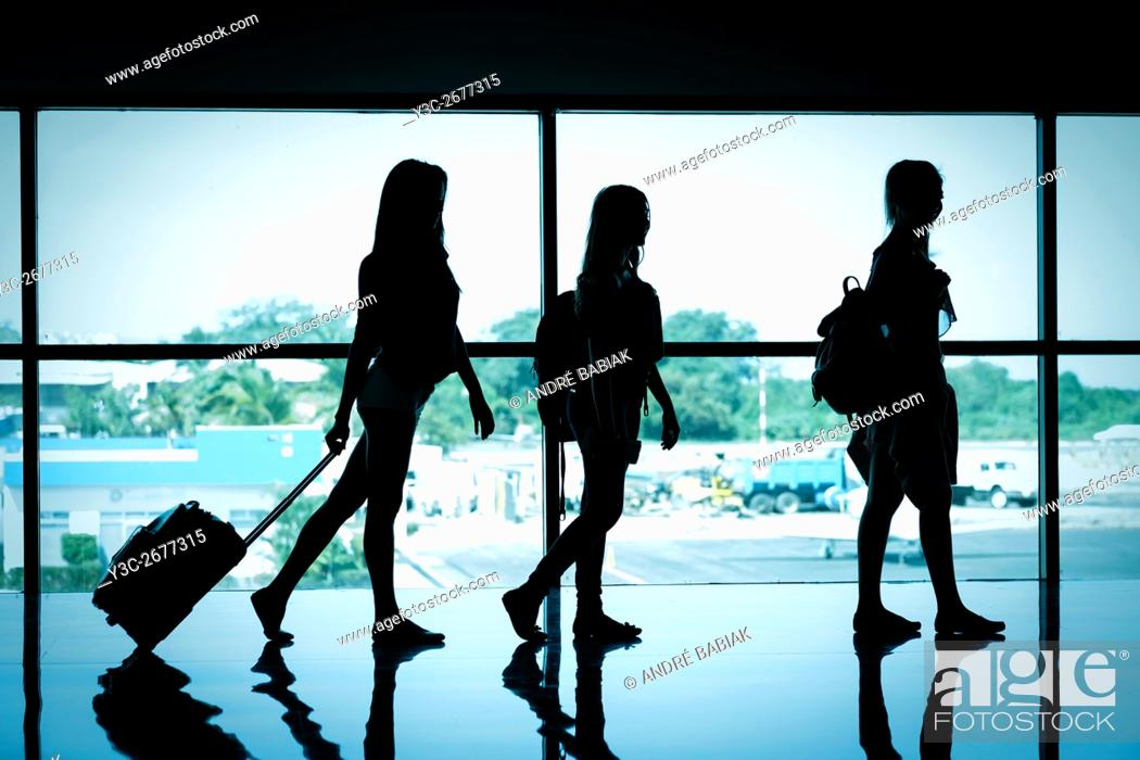 Stock Photo: Silhouette of 3 female travelers at airport terminal.
