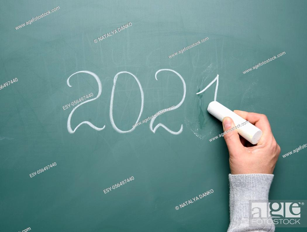 Stock Photo: female hand holds a piece of white chalk and writes on a green school board 2021, new year.