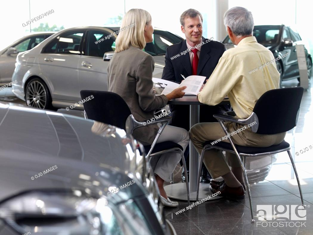 Stock Photo: Salesman talking to couple in automobile showroom.