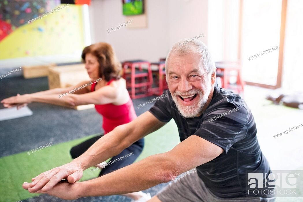 Stock Photo: Senior man and woman exercising in gym.