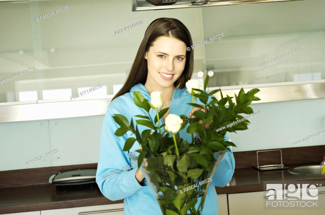 Stock Photo: Young smiling woman filling vase with roses.