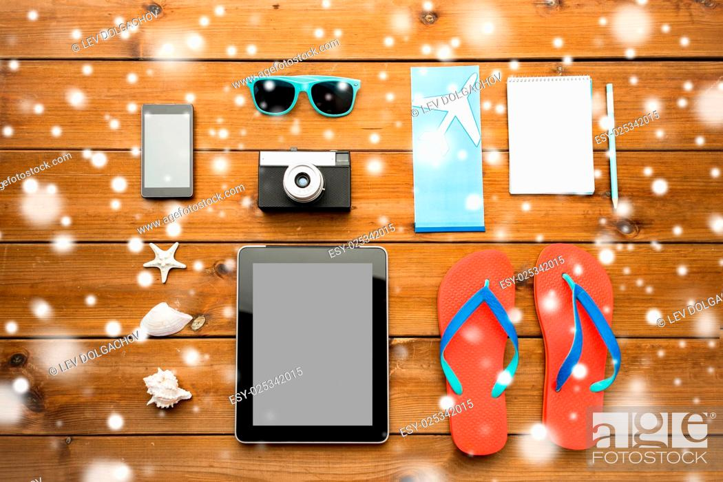 Stock Photo: vacation, tourism, winter holidays and objects concept - close up of tablet pc computer and travel stuff.