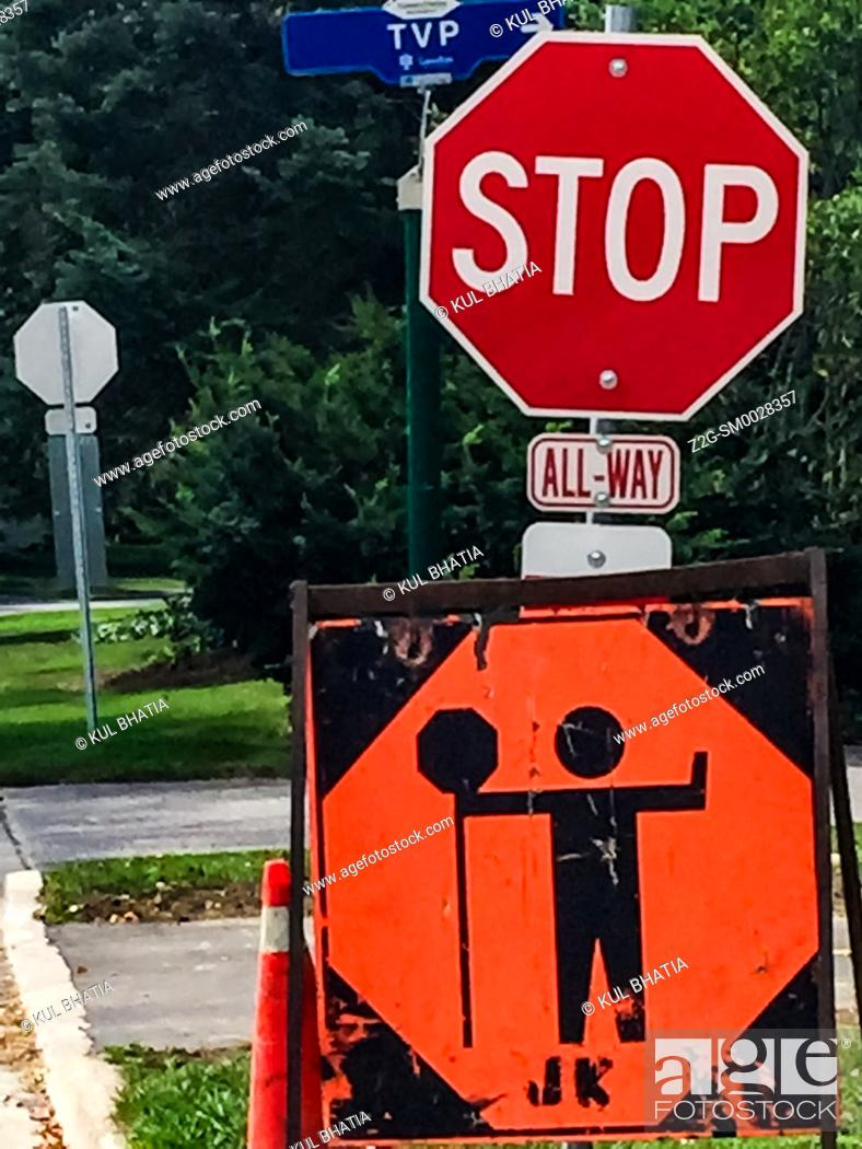 Stock Photo: STOP sign indicating the presence of a guard directing traffic ahead at a road work site, Ontario, Canada.