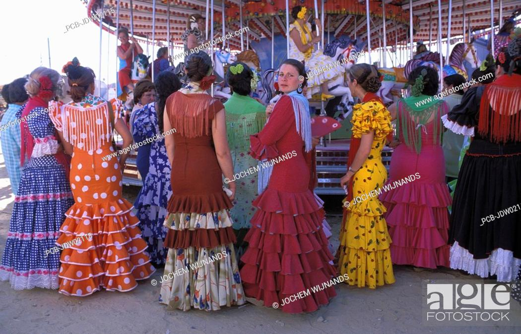 Stock Photo: Sanlucar de Barrameda, a group of women in flamenco dress watching a merry go round.
