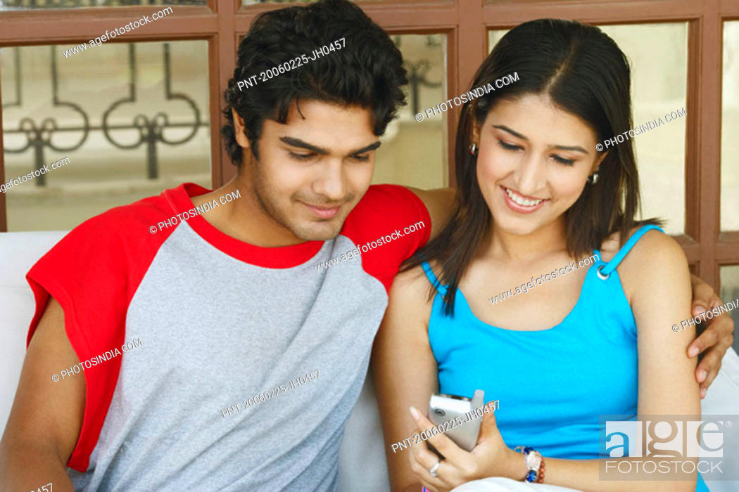 Stock Photo: Close-up of a young couple sitting together holding a mobile phone.