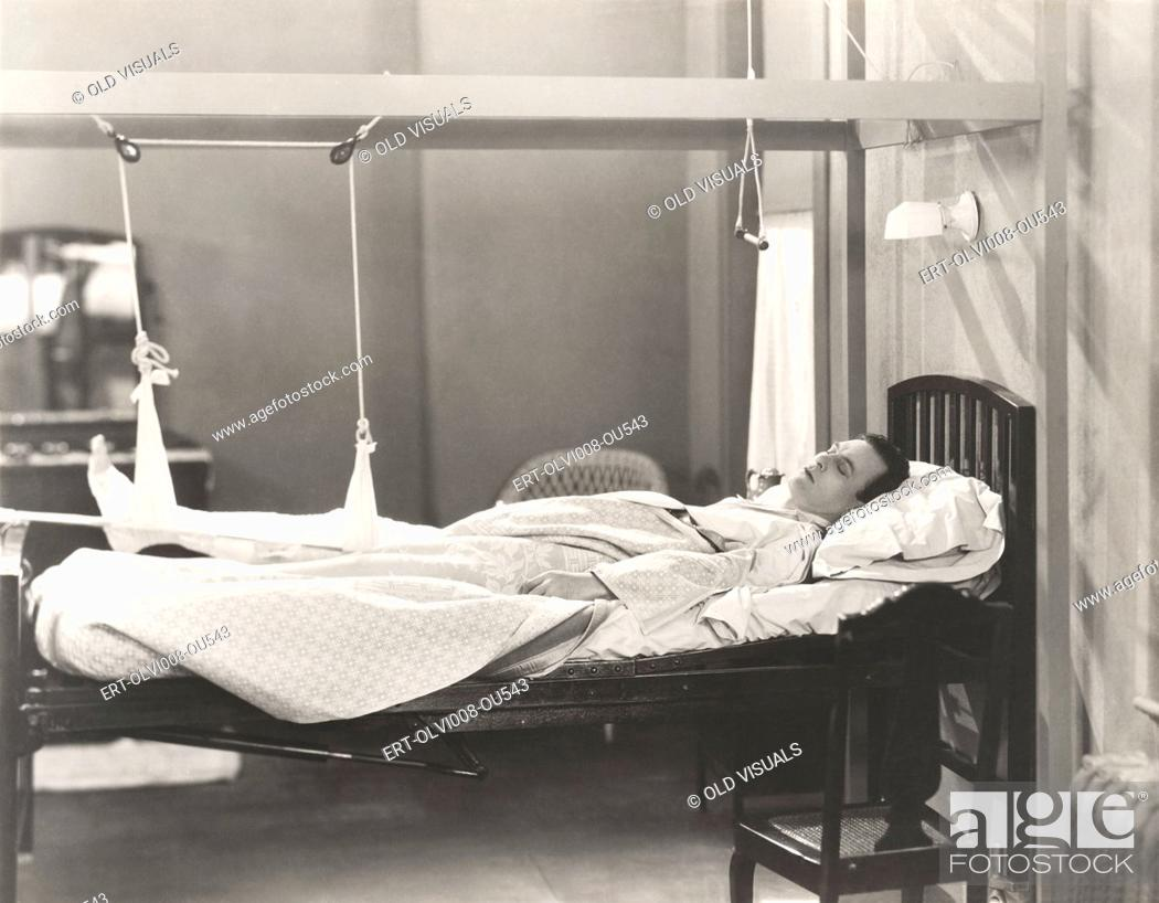 Stock Photo: Man with fractured leg sleeping on hospital bed.