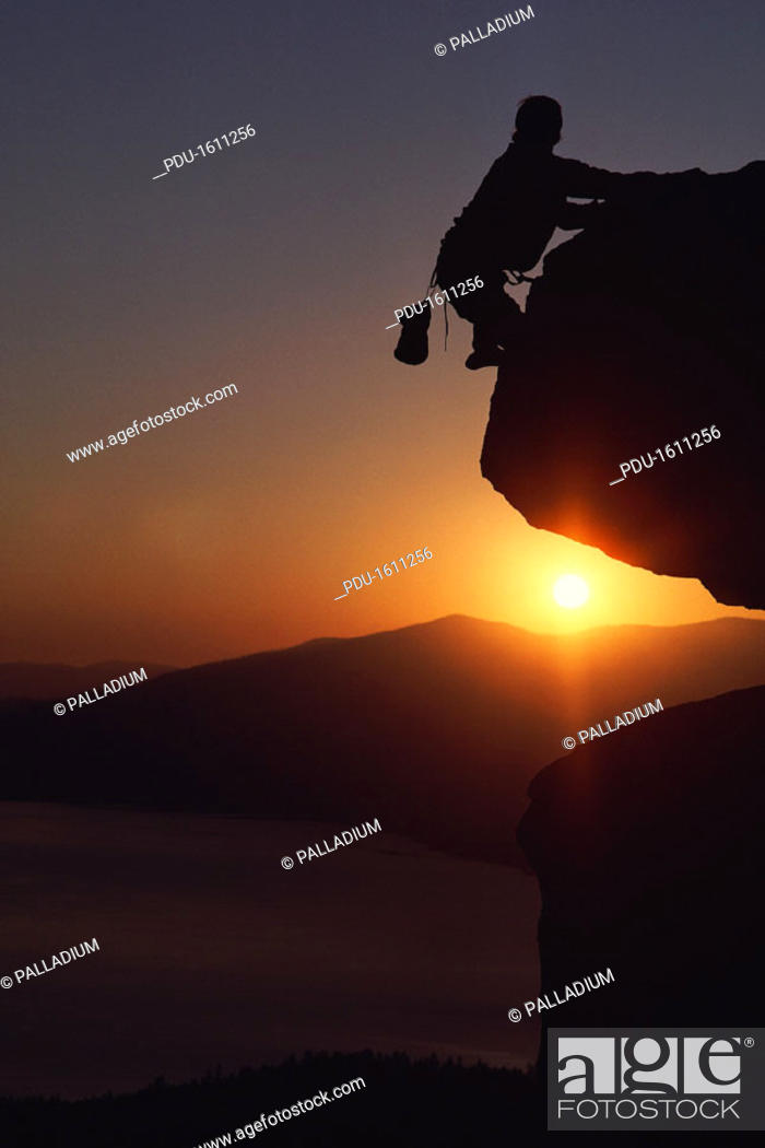 Stock Photo: Silhouette of rock-climber at sunset.