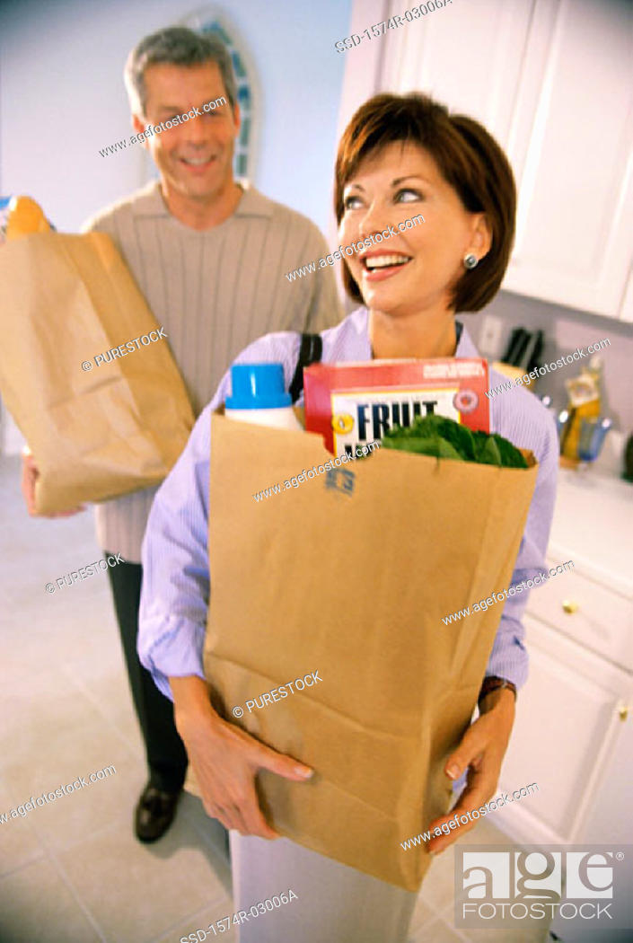 Stock Photo: Mid adult couple standing in a kitchen holding grocery bags.