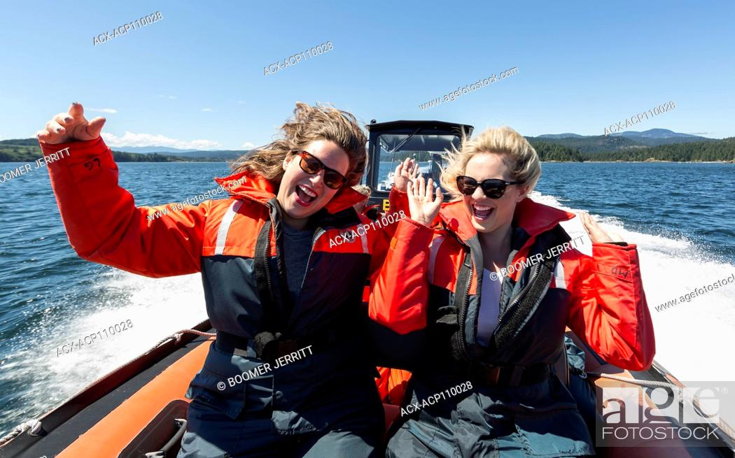 Stock Photo: Two friends take in the experience of a whale watching trip from the front of their zodiak just south of Seymour Narrows.
