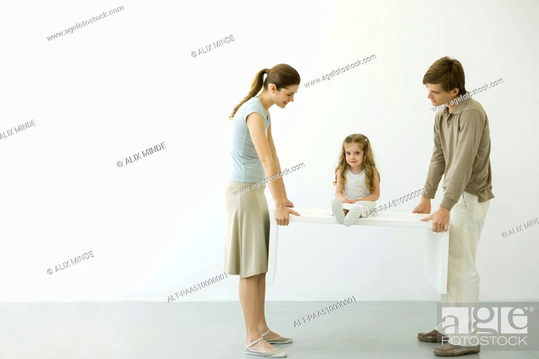 Stock Photo: Young couple carrying table with daughter sitting on it.
