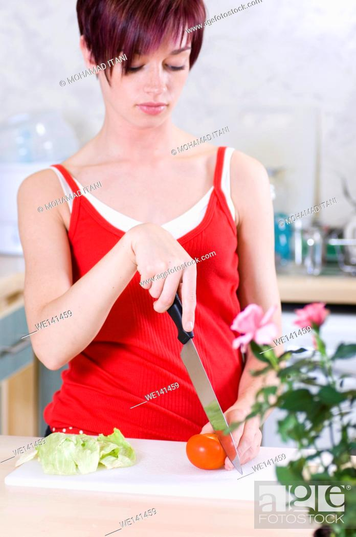 Stock Photo: young woman making salad.
