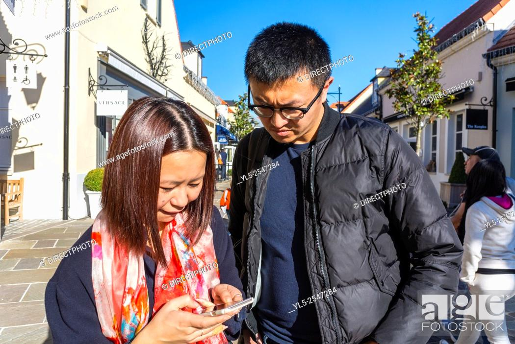 Imagen: Paris, France, Chinese Couple Tourists Shopping in Luxury Stores in La Vallee Village, Discount Shops, using Iphone on Street M.R.