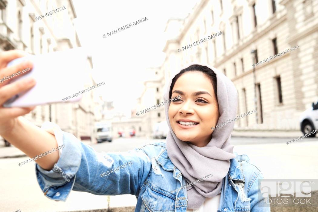 Stock Photo: UK, England, London, young woman wearing hijab taking a selfie in the city.