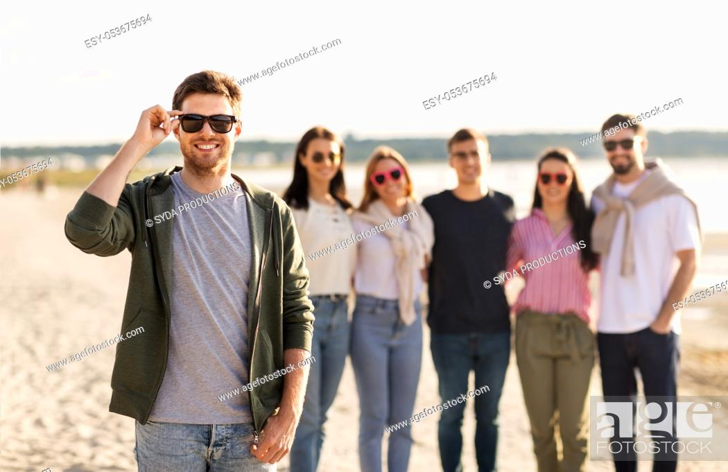 Stock Photo: man in sunglasses with friends on beach in summer.