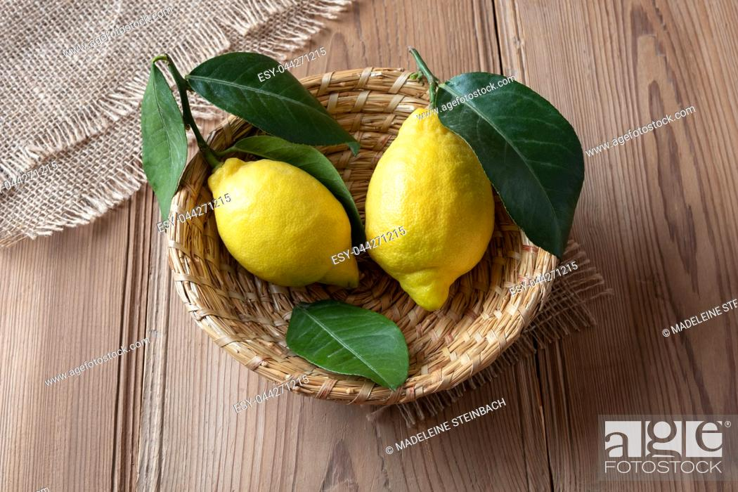 Stock Photo: Two fresh lemons with leaves in a basket.