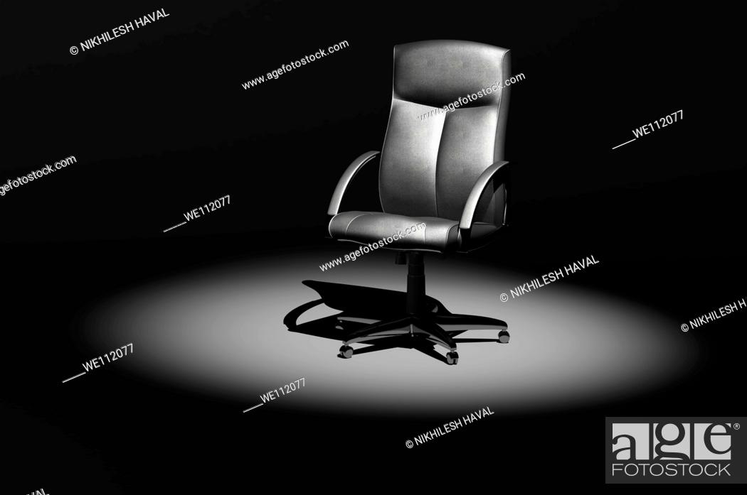 Stock Photo: Leather office executive chair in spotlight 3D.
