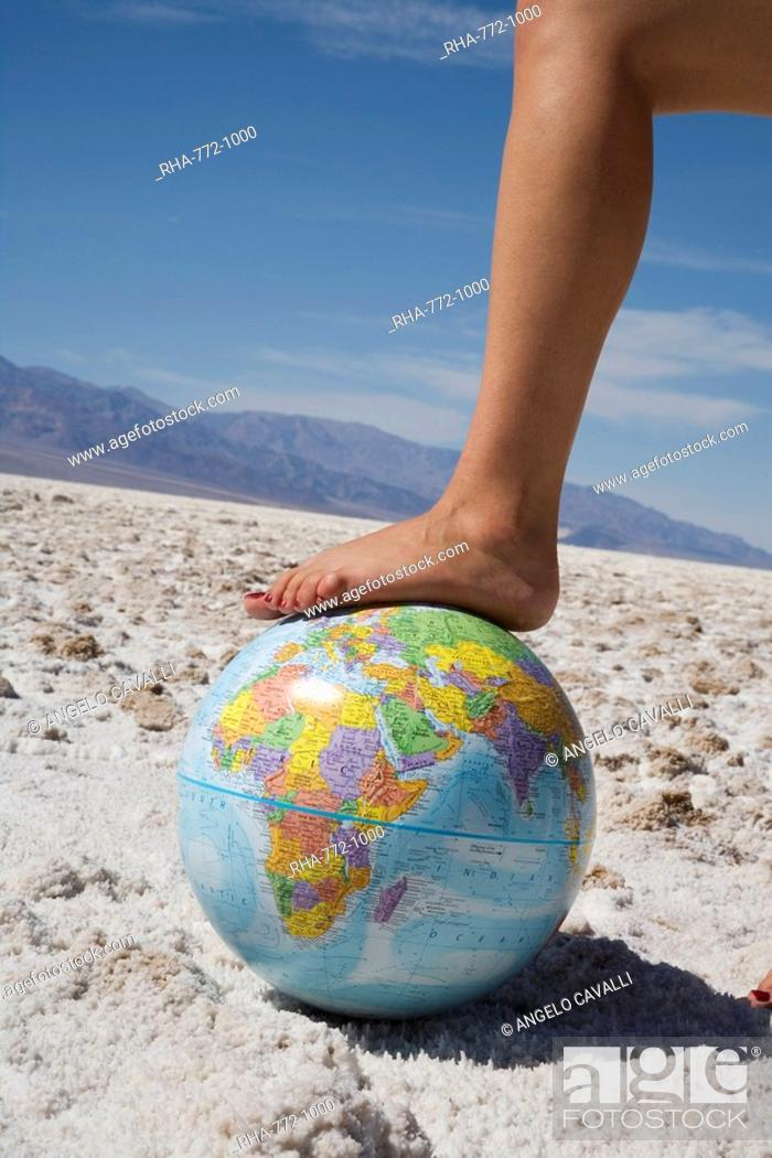 Stock Photo: Woman's foot on globe, Bad Waters Point, Death Valley National Park, California, United States of America, North America.