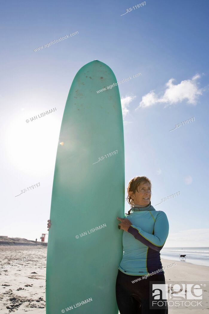 Stock Photo: Senior surfer with board on sandy beach.