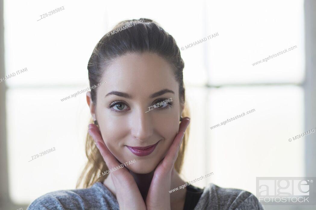 Stock Photo: Beautiful young woman hands touching face smiling.