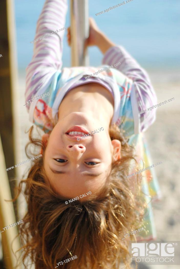 Stock Photo: Cute seven year old brazilian girl, playing on the beach of Santa Eulalia del Rio, Ibiza, Spain, during a beautiful and sunny day.