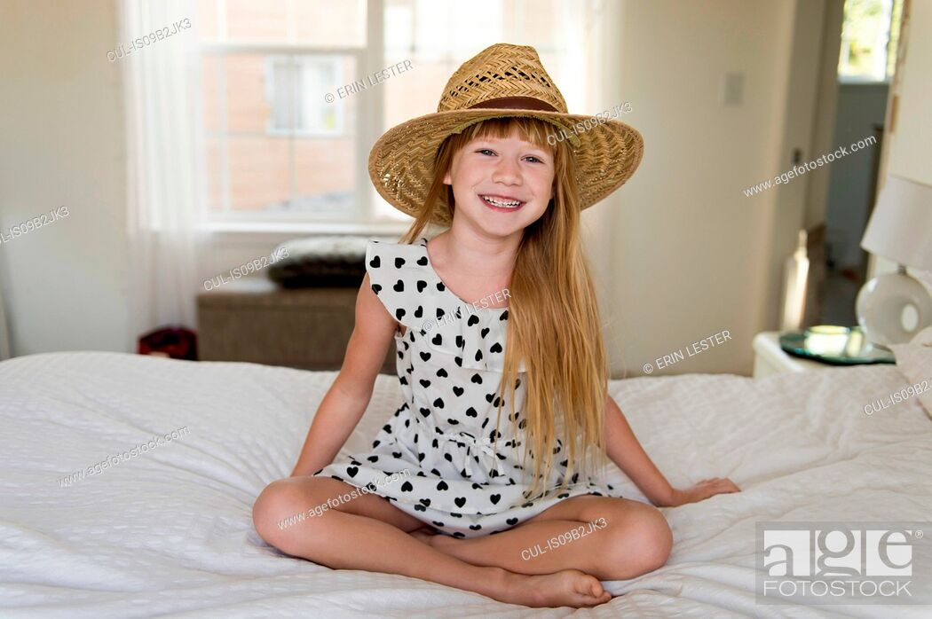 Stock Photo: Young girl sitting on bed smiling, wearing straw hat.