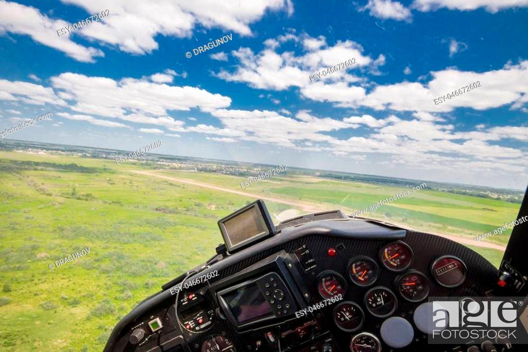 Stock Photo: View from the cockpit of a light private plane while performing a leisure flight in summer.