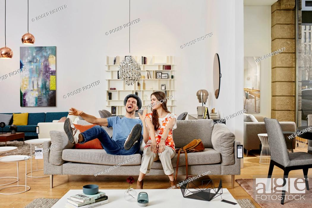 Stock Photo: Couple in modern furniture store testing couch, being happy.