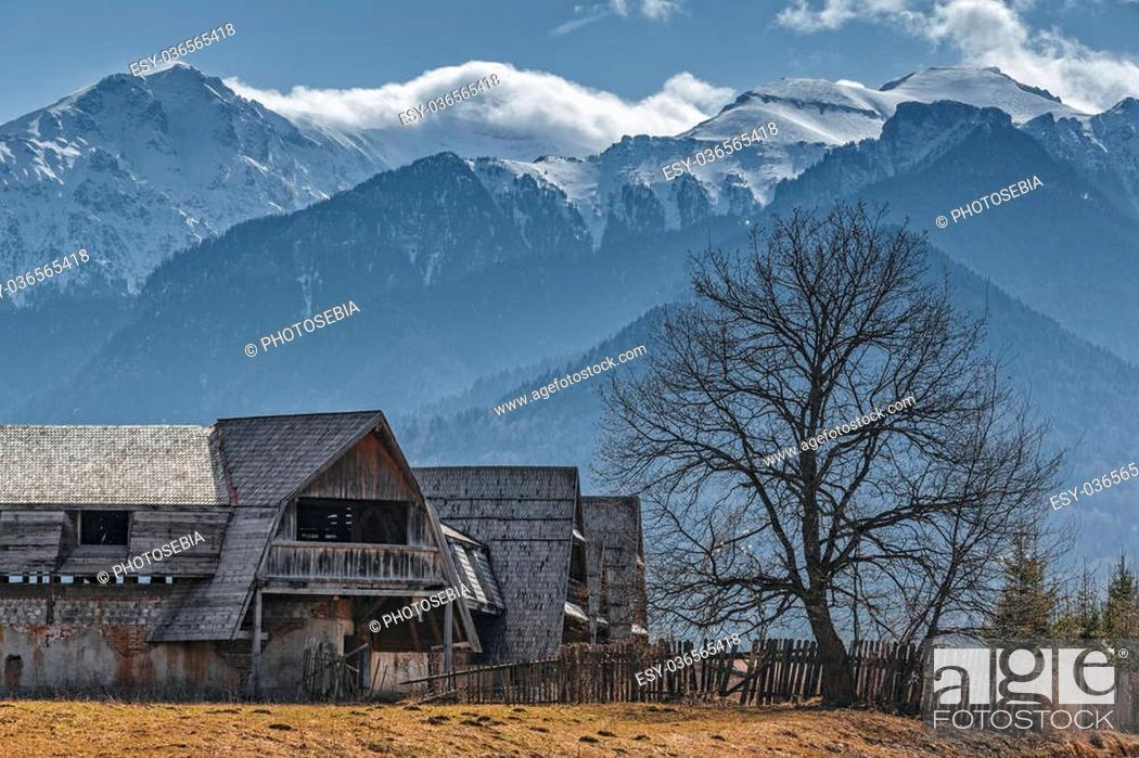 Stock Photo: Rural scenery with old abandoned wooden farmhouse in the valley of snowy Bucegi mounains, Brasov county, Romania.