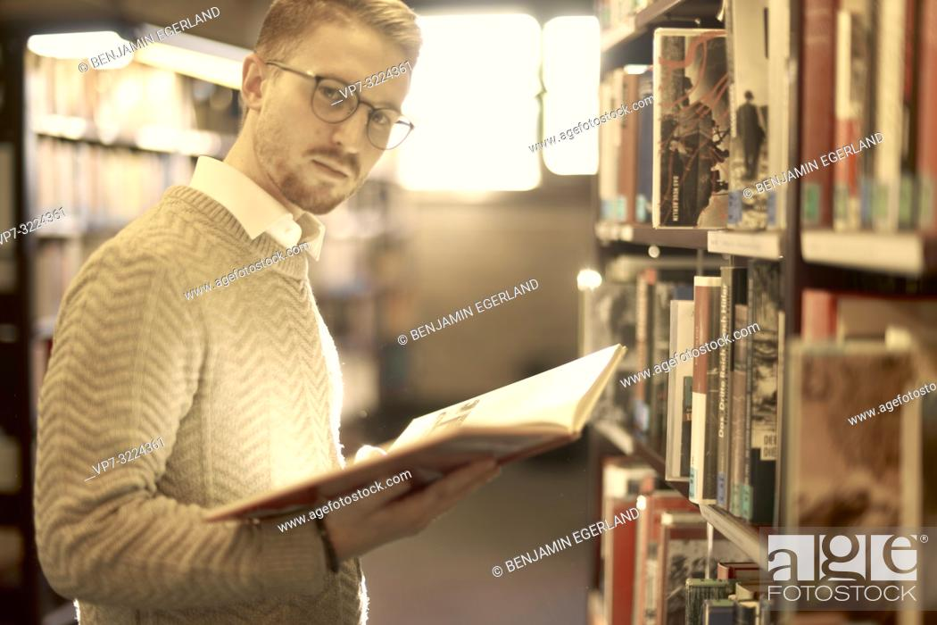 Stock Photo: man holding book, library, glasses, student, university, knowledge.