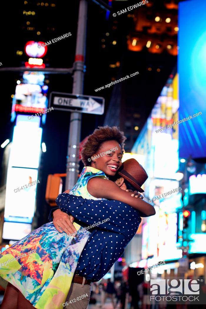 Stock Photo: Couple hugging on city street at night.