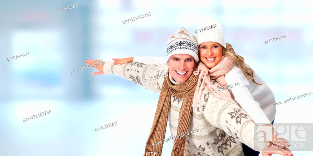 Stock Photo: Happy smiling couple in love over blue winter background.