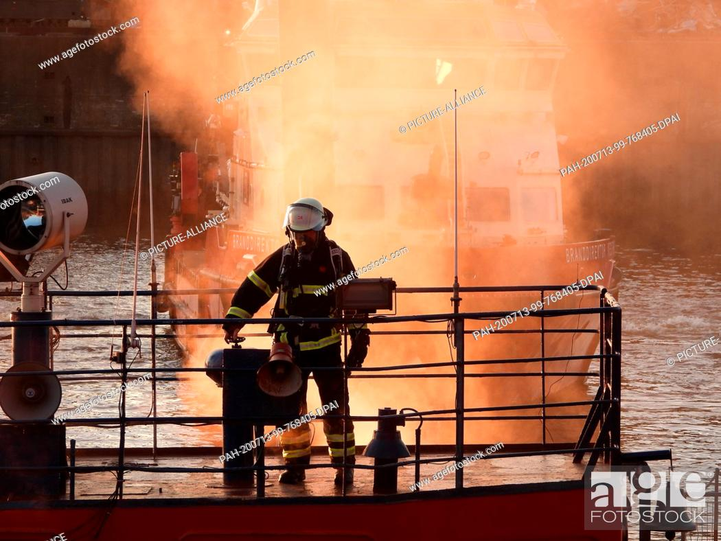 Stock Photo: 13 July 2020, Hamburg: A firefighter is in action on deck from a floating crane. Due to a fire on a floating crane in Hamburg-Steinwerder.