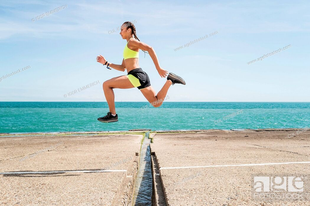 Stock Photo: Young woman running outdoors, jumping over gap in bridge, mid air.