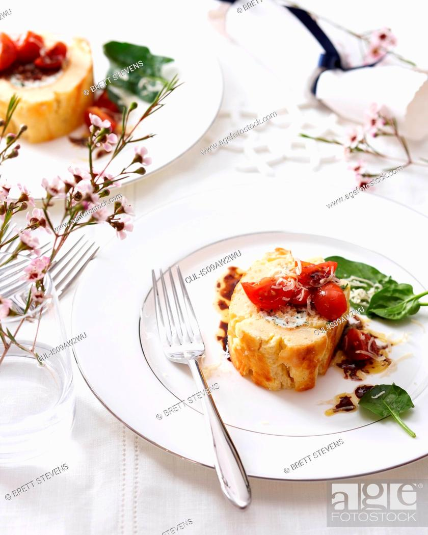 Imagen: High angle view of goat cheese roulade with tomatoes and basil on elegant plate.