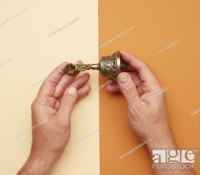 Stock Photo: male hands hold a copper Tibetan ritual bell, bell represents the feminine principle of excellence in wisdom, top view.