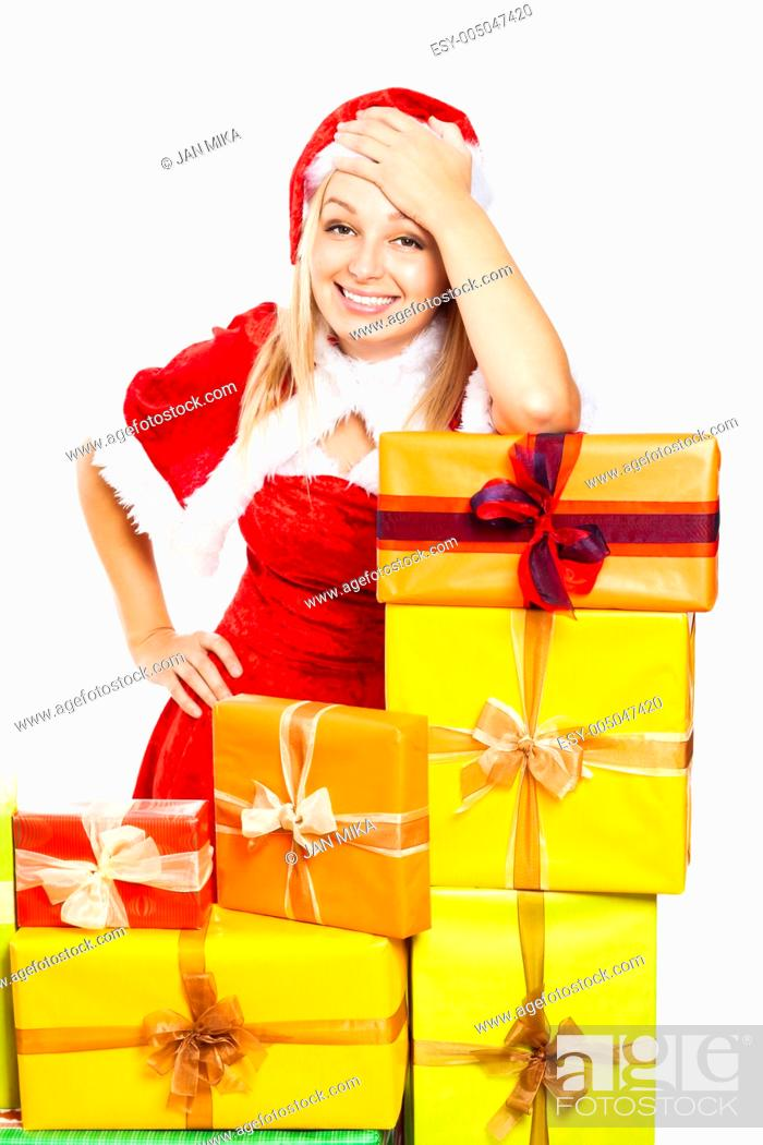 Stock Photo: Young beautiful blond happy smiling woman in Santa costume surrounded by Christmas gift boxes, isolated on white background.