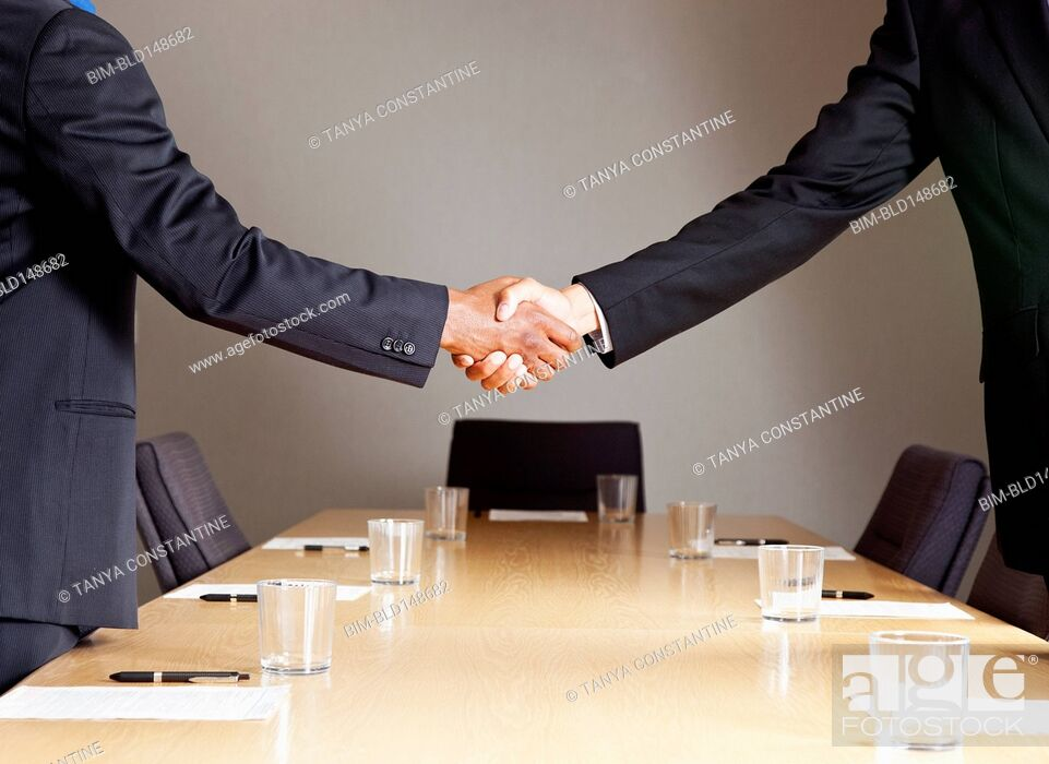 Stock Photo: Mixed race businessmen shaking hands in conference room.