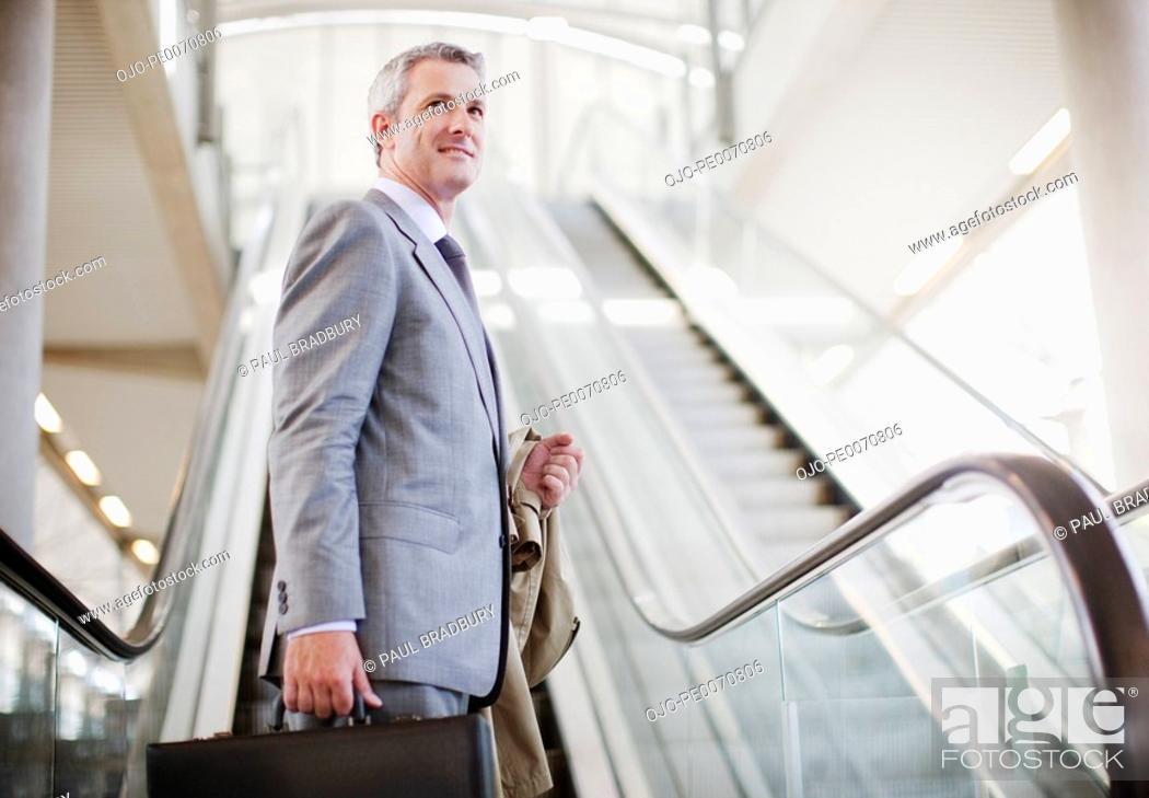 Stock Photo: Businessman standing near escalator.