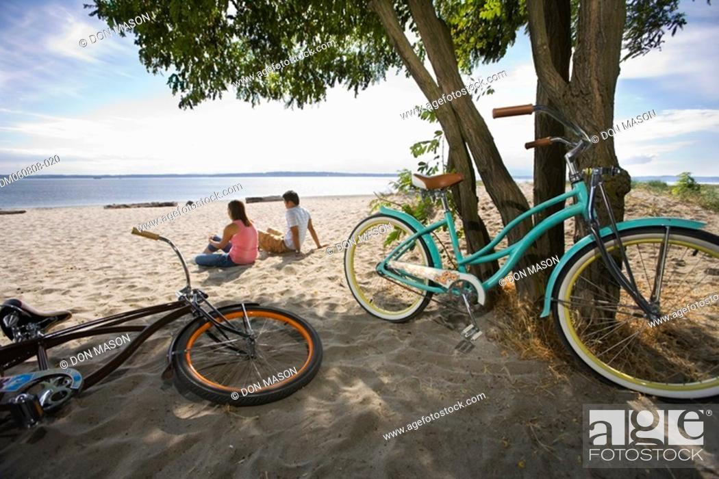 Stock Photo: Pacific Islander couple sitting on beach with bicycles.