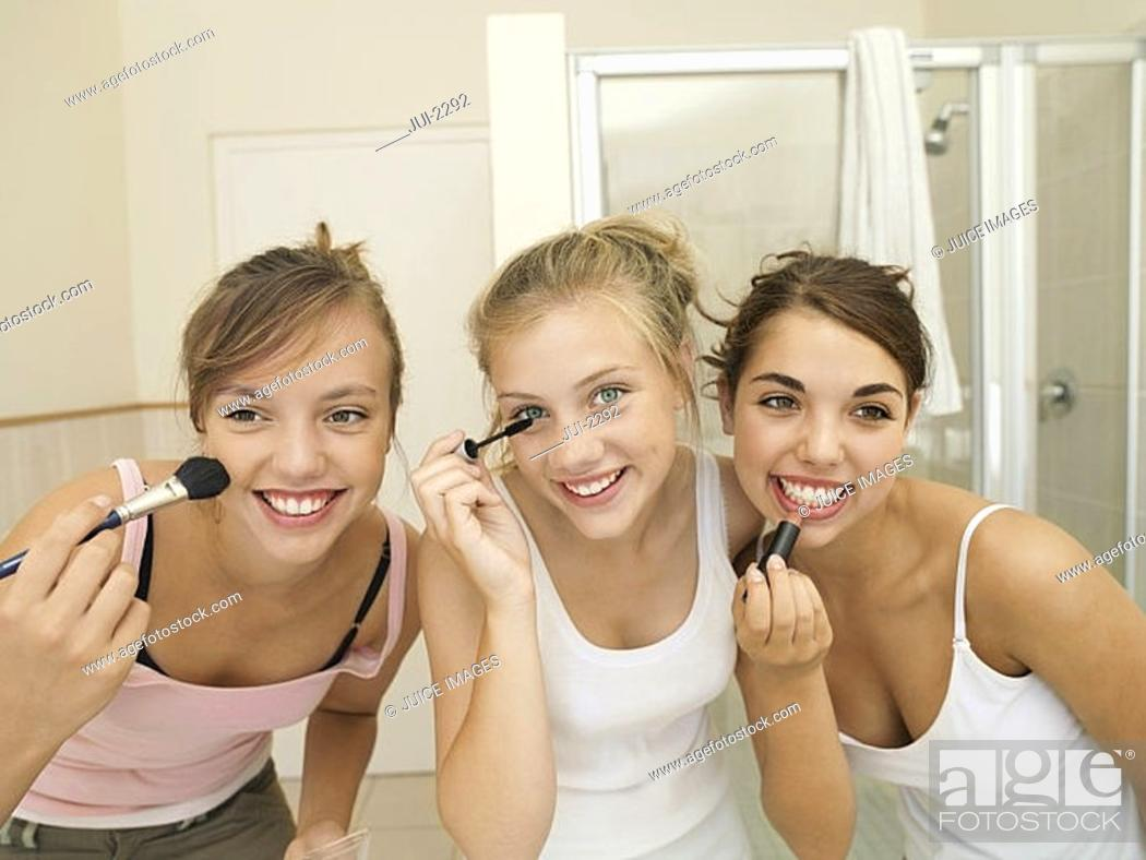Stock Photo: Three teenage girls 15-17 applying make-up in bathroom, smiling, front view, close-up.
