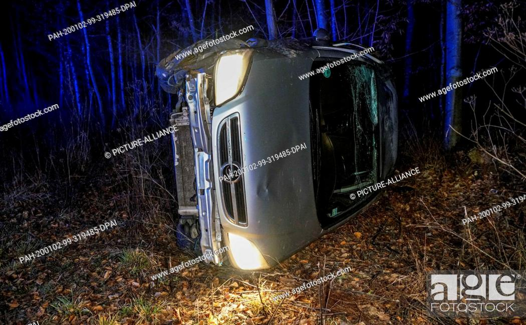 Stock Photo: 01 January 2020, Baden-Wuerttemberg, Esslingen: On New Year's Eve a car is lying on the driver's side after a black ice accident in a forest.