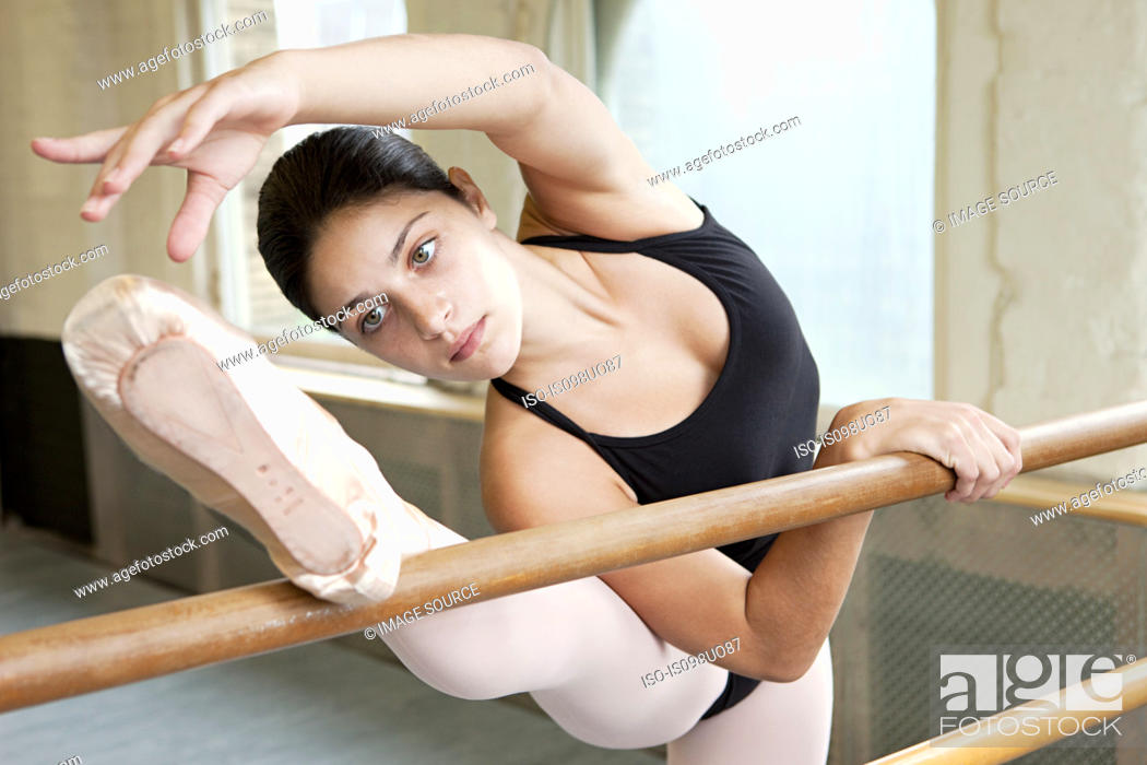 Stock Photo: Ballerina stretching at barre.