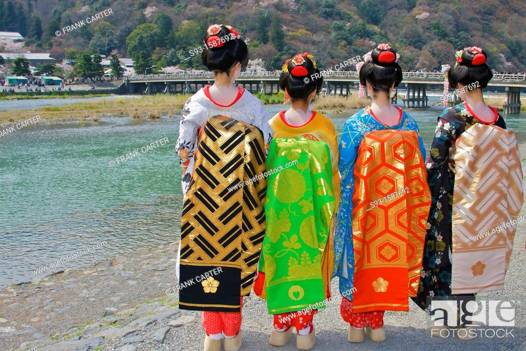 Stock Photo: Tourists dressed up as geisha in front of the famous Togetsu-kyo bridge over the Katsura river, rear view.