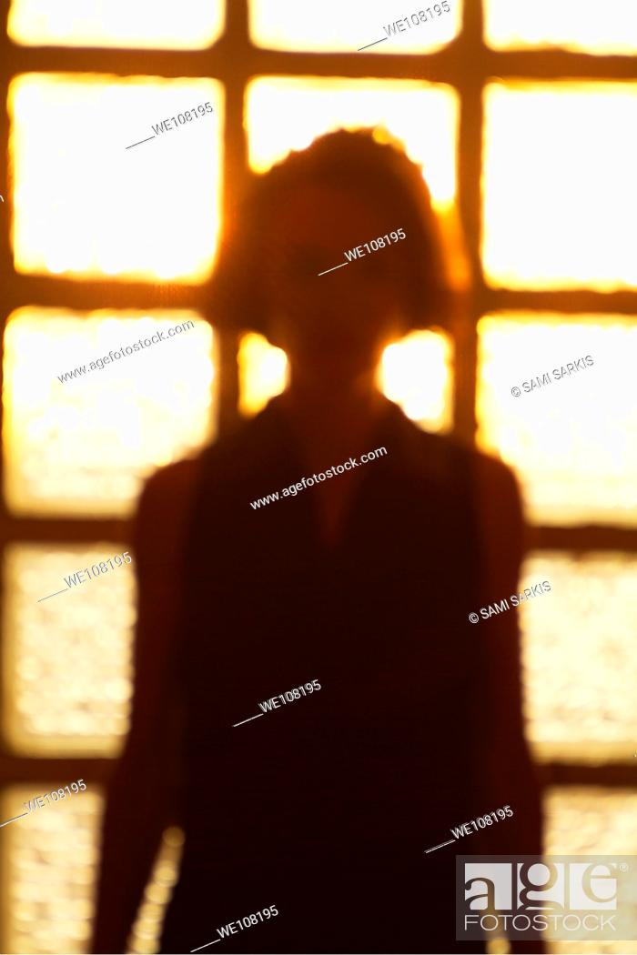Stock Photo: Silhouette of a woman standing in front of a window, France.