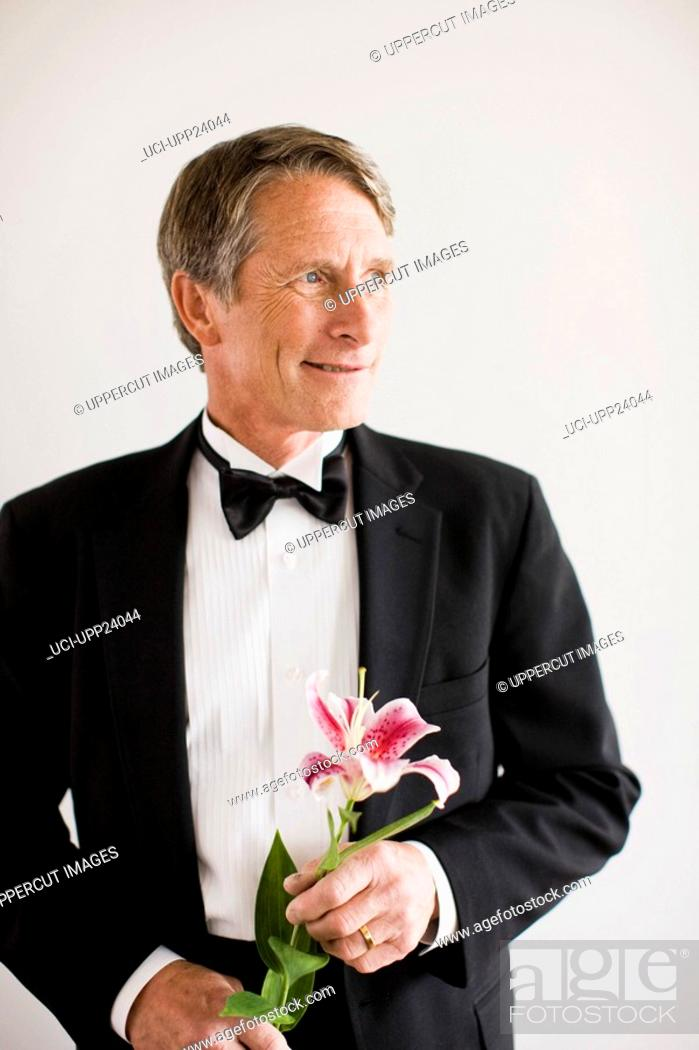 Stock Photo: Portrait of man in tuxedo holding Oriental lily.