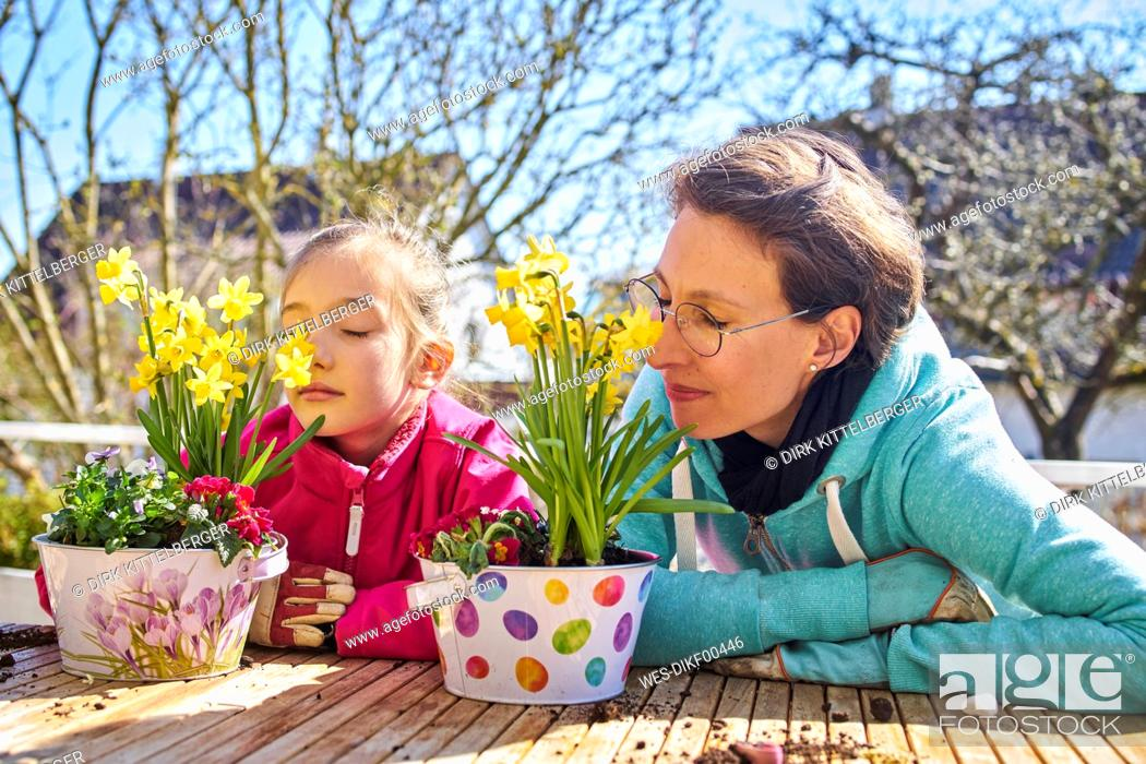 Stock Photo: Mother and daughter smelling flowers on balcony.