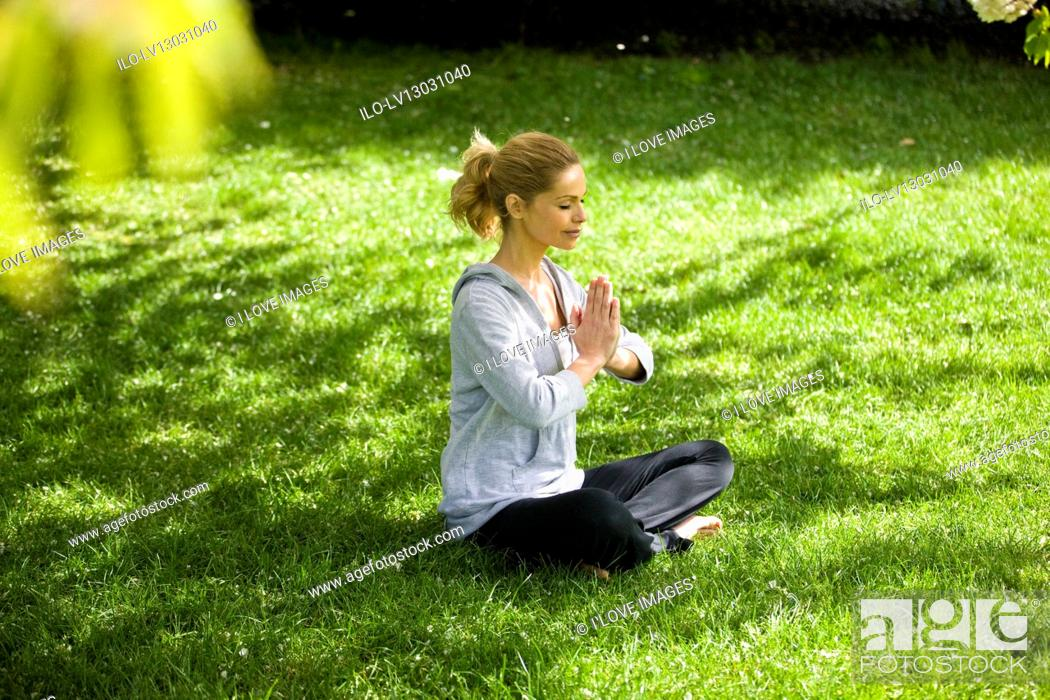 Stock Photo: A mid adult woman meditating in the park.